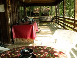 Huxley house photo - Covered front porch overlooking the lake, table, swing, rockers