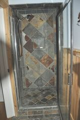 Stratton Mountain farmhouse photo - first floor shower with natural slate stone tiled throughout this full bath