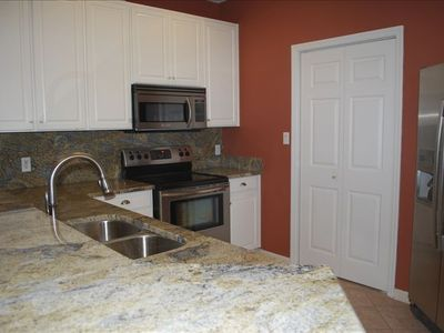 Beautiful kitchen with stainless steel appliances, granite counter tops.