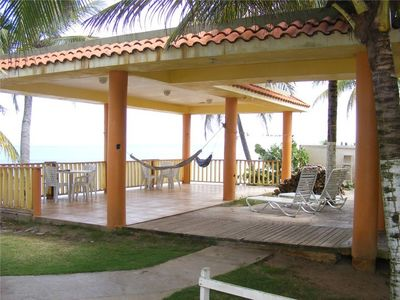Wide terrace in front of the beach with hammocks and BBQ.
