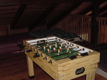 Fooseball table in the loft with three queens on the floor and hard to see.