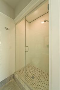 Premium finishes throughout, like this frameless glass shower with marble floor.