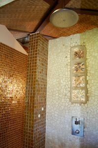 Walk in gold tiled shower with a wonderful rain shower.