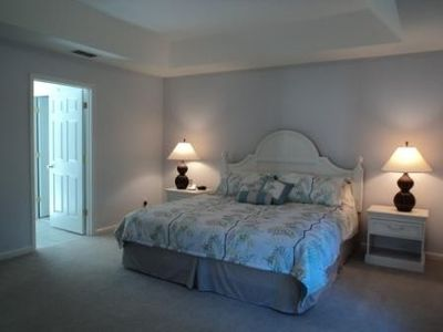 Master bedroom with king-size bed has large bathroom, walk-in closet