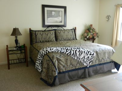 Spacious master bedroom with king sized bed, flat screen tv