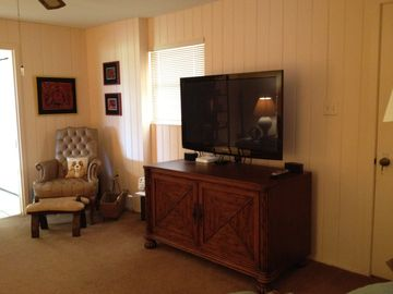 Den with chairs, couch and large flat screen TV, DVD/VCR player