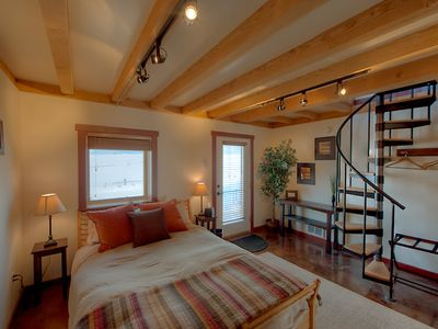 The cozy bedroom has timbered ceilings and a queen size bed.