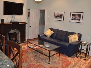 Capitol Hill townhome photo - Living room & dining area, w/sleeper-sofa, HDTV and entry to private bedroom.