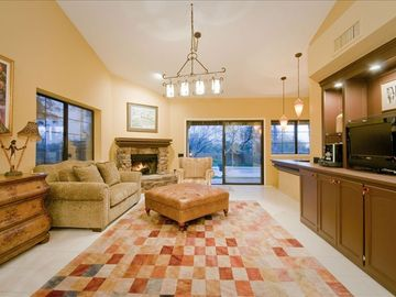 View of Family Room with Fireplace and Wet Bar from Kitchen