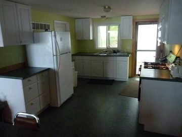 recently remodeled kitchen, gas stove, microwave, fridge, large dining table