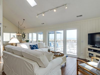Open living, dining and kitchen areas with large oceanfront deck.