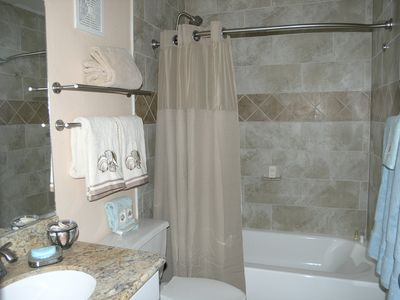 Tiled bath with rain showerhead, curved shower rod, new tub, new toilet. Clean.