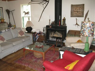 Woodburning fireplace, two couches, antiques and art surround you. Curl up!