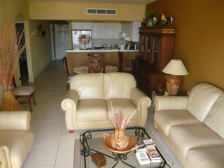 Puerto Vallarta condo photo - Living room with leather couches and Flat Screen TV, dining area, and kitchen