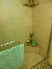 Kihei condo photo - Updated tile shower with granite seat and glass sliding door.