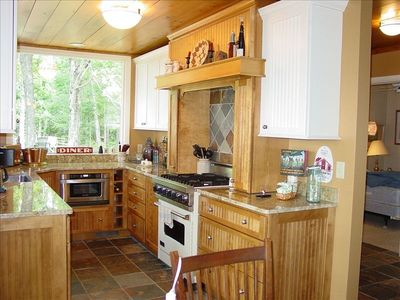 Gourmet kitchen features professional range, granite countertops, great views