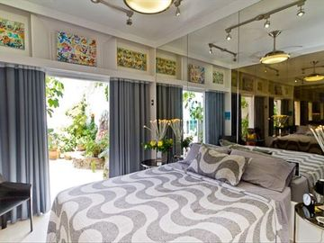 Master bedroom has mirrored walls, queen bed, and opens to large covered patio