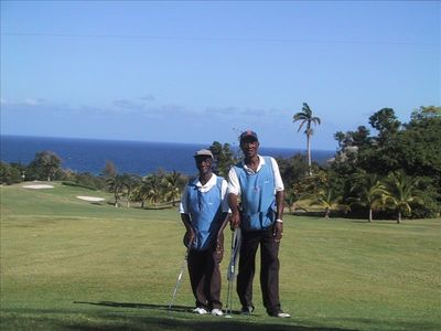 Two of Tryall's fine caddies posing on the 14th hole with its vast view of the S
