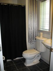 Main Level Twin Bedroom Bath w/ shower, pedestal sink, toilet - Lake Anna house vacation rental photo