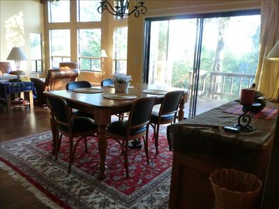 the dining room and living room looks out to the deck and the mountains.