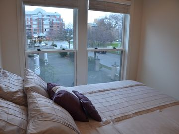 Comfortable queen size bed in the 2nd bedroom with a view to the park