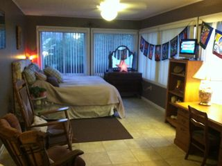 Sunroom/Bedroom 2 - Large room with King bed, futon, tv, rockers, and lake view.