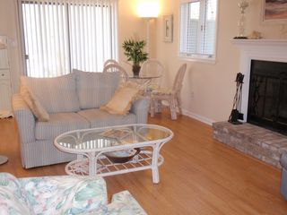 Bethany Beach townhome photo - The living room features sliding glass doors and a wood burning fireplace.
