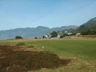 View of golf links with mountain ranges in the distance