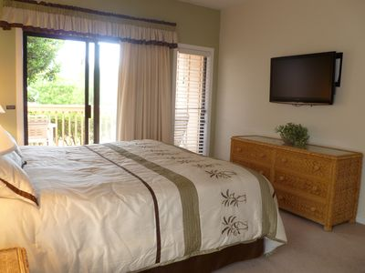 Master bedroom with king bed, flat screen TV, and door to lanai