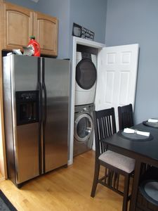 stainless steel refrigerator and stacked laundry hardwood floors through out