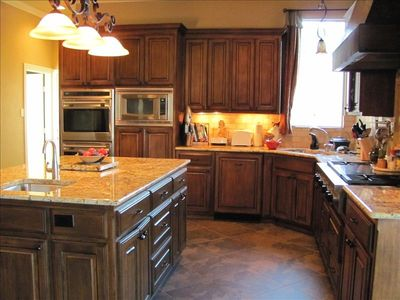 Kitchen has granite countertops and steel appliances, with two convection ovens.