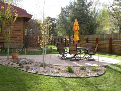 Large fenced yard with patio opens to  acres of opportunity to hike and play.