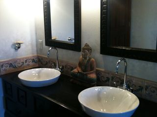 Papaikou studio photo - .Double vanity sinks in the bathroom atop an Indonesian furniture piece.