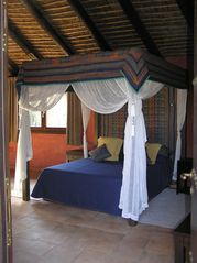 Cortes de la Frontera villa photo - Romantic four poster bed in one of the natural stone, thatched roofed cottages