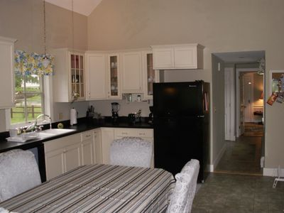 Kitchen includes dishwasher, fridge, microwave and leads to main living area