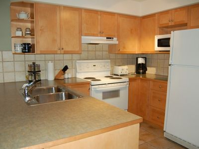 Lovely kitchen w/ maple cabinets and tile floor. Cupboard stocked w/ condiments