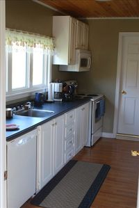 Well equipped kitchen with pantry beyond and washer/dryer.