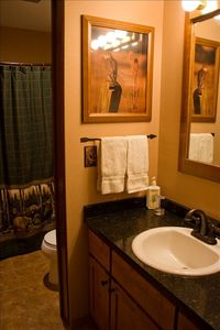 Vanity area with glimpse of toilet and tub with shower curtain