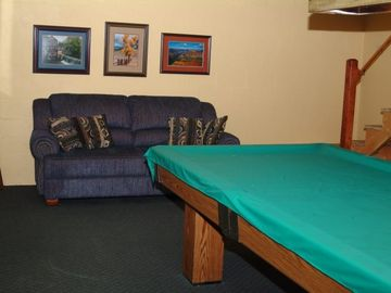 Game room has a full size pool table, a set of bulk beds, loveseat and stereo