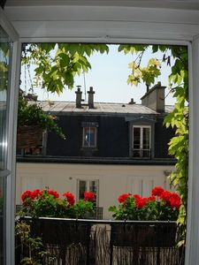 a flower-laden balcony at each window