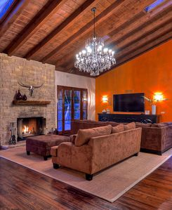 Great room fireplace with large comfortable couches and french doors to pool.