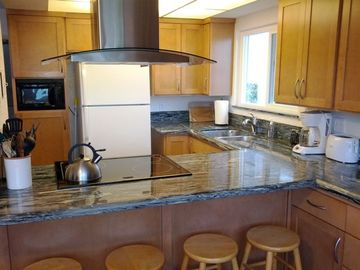 Newly remodeled kitchen with sea wave granite counter tops and breakfast bar.