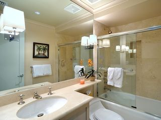 The nicely detailed second bathroom has a tub and shower with glass doors. - Key West condo vacation rental photo