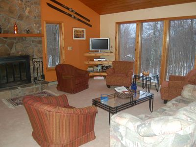 Great Room with plenty of seating, a stone fireplace and a wonderful view!