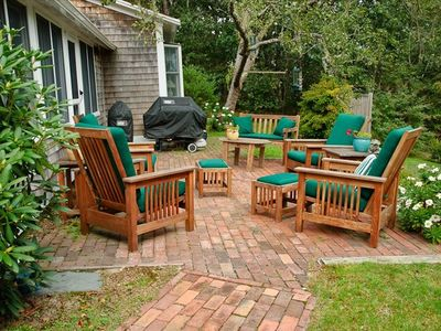 Teak furniture on patio; grills, outdoor shower,  tree stump in background