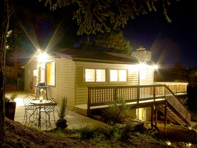 The Fir House – Nighttime view overlooking wrap-around deck and patio with bbq.