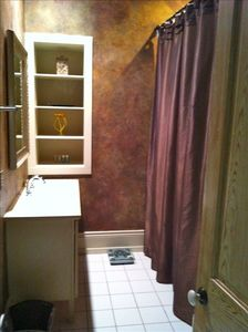 Guest bathroom with custom wall treatment,satin shower curtains,large showerhead
