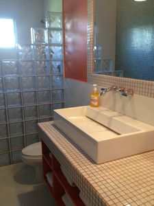 Remodeled bathroom with large sink and mirror, shower with clear glass blockwall