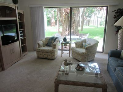 "Living room with 40"" flat screen TV and DVR with view of Banyan trees outdoors"