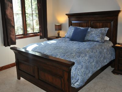 Queen size bed with large closet and bathroom across the hall